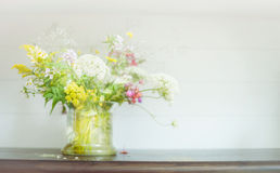 Wild flowers bunch in glass pot  on wooden shelf at light background. Floral Home decoration Stock Photo