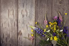 Wild flowers on old grunge wooden background chamomile lupine d. Andelions thyme mint bells rape Stock Photos