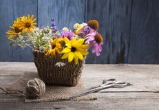 Wild flowers and scissors on old grunge wooden background chamo. Wild flowers tangle of rope and scissors on old grunge wooden background chamomile lupine Royalty Free Stock Image