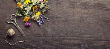 Wild flowers and scissors on old grunge wooden background chamo. Wild flowers tangle of rope and scissors on old grunge wooden background chamomile lupine Stock Photo