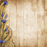 Wild flowers with spikelets on a wooden background. Border of wildflowers, spikelets, chamomiles, cornflowers and poppies on a wooden background with space for Royalty Free Stock Images