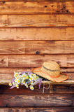 Wild flowers with straw hat on old boards. Background Stock Photo