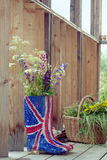 Wild flowers in Union Jack rubber boots-wellies. Bunch of wild flowers in Union Jack rubber boots-wellies on a country house wooden porch, natural outdoor shot Stock Photos