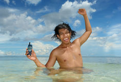 Wild fun in tropical sea. Asian teenager in a tropical sea shouting and cheering loud having fun and holding a cellphone with clenched fist in the air Stock Photo