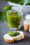Wild garlic pesto. Glass of wild garlic pesto and fresh baguette Royalty Free Stock Photography