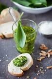 Wild garlic pesto. Glass of wild garlic pesto and fresh baguette Royalty Free Stock Photos