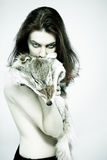 Wild girl. Fashion exotic portrait: young attractive naked girl with wolf`s fell looking wild to camera Royalty Free Stock Photography