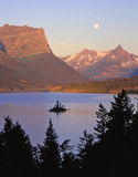 Wild Goose Island & Full Moon. The full moon over Wild Goose Island, in Saint Mary Lake, located on the Going to the Sun Road in Wyoming's Glacier National Stock Photography