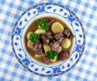 Wild goulash with potato, sauce on blue plate Royalty Free Stock Image