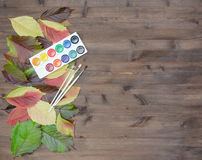 Wild grapes multicolored autumn leaves paints and brushes Royalty Free Stock Photos