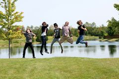 Wild Guys. Group of teen boys jumping by a lake stock photography