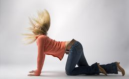 Wild hair. Young woman kneeling on floor, hair flying wildly Stock Images