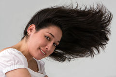 Wild hair. A beautiful latina lady with wild hair blowing to the front, isolated on white/gray Royalty Free Stock Photography