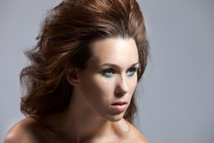 Wild hairstyle. Beautiful brunette with a wild hairstyle looking intense Royalty Free Stock Images