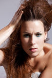 Wild hairstyle. Beautiful woman with wild hairstyle on grey background Stock Image