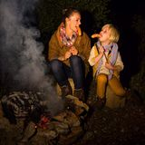 Happy mother and daughter tourists eating grilled sausages Stock Photo