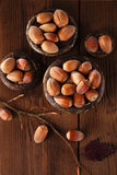 Wild hazelnut in iron bowls on wooden table Royalty Free Stock Image