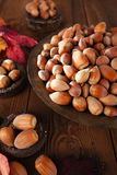Wild hazelnut in iron bowls on wooden table Stock Photo