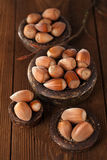 Wild hazelnut in iron bowls on wooden table Stock Images