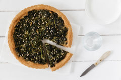 Wild herb spinach quiche, vegetarian. On white wooden background Royalty Free Stock Photo