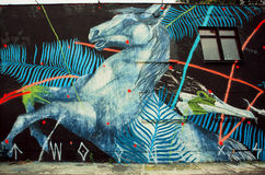 Wild horse by unknown artist on rustic street wall with graffiti Royalty Free Stock Photos