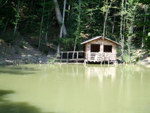 Wild house on the lake in the mountains Royalty Free Stock Image