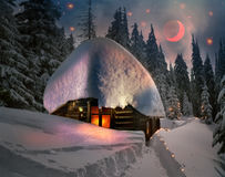 Wild hunting lodge. Climbing to tourist wild alpine mountain to an abandoned cabin-in order to illuminate the snow-covered spruce canopy during moonrise, moonset Royalty Free Stock Image