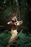 Wild huntress with bow. In the woods. Power and survival Royalty Free Stock Photos