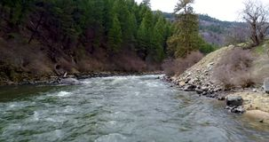 Wild Idaho river with a bridge designs for trains. Following a wide river under a train bridge stock footage