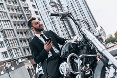 Wild inside. Good looking young man in full suit using his smart phone and looking away while sitting on the motorbike outdoors Stock Photography