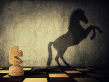 Wild knight. Magical transformation as a wooden knight chess piece casting a shadow of a wild horse on two legs on the wall. Symbol of business aspirations royalty free stock photo