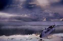 Wild landscapes. Kayak on the shore of a large lake surrounded by snow-capped mountains Stock Photo