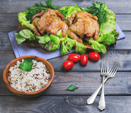 Wild and long grain white rice in a wooden bowl, two baked chick. En, lettuce, parsley and cherry tomatoes on a gray wooden background royalty free stock images