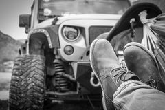 Wild Luxury. An offroad jeep in the background while someone`s shoes are visible who is relaxing on a hammock Royalty Free Stock Photo
