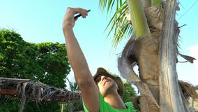 Wild man climbing on tree and trying to make a connection on his cell phone. Accident shipwreck lack of civilization.  stock video footage