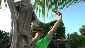 Wild man climbing on tree and trying to make a connection on his cell phone. Accident shipwreck lack of civilization.  stock footage