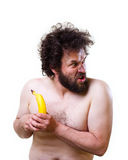 Wild man looking confused at a banana. Wild, undressed man with crazy hair and beard, holding a banana in his hands Stock Photo