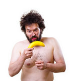 Wild man looking confused at a banana. Wild, undressed man with crazy hair and beard, holding a banana in his hands Stock Image