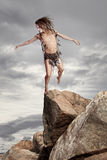 Wild man stands on a rock Royalty Free Stock Image