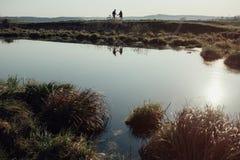 Wild meer in de achtergrondsilhouetten van twee mensen stock foto