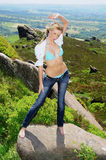 Wild on the moors. Stunning blond model poses with open shirt on a boulder in the open moors Royalty Free Stock Images