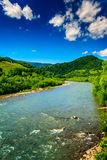 Wild mountain river on a clear summer day. Wild river flowing between green mountains on a clear summer day Royalty Free Stock Photos