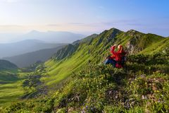 Among the wild mountains flowers at the edge of the cliff there is a girl sitting and watching the peaks of mountains. Royalty Free Stock Photos