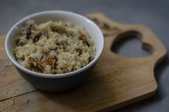 Wild mushroom risotto. Bowl of wild mushroom Risotto on a wooden board with grey background Royalty Free Stock Photo