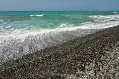 Wild natural beach with mostly dark pebble stones, sea and sky in background.  stock images