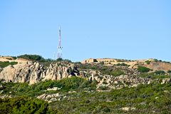Wild nature landscape of  mountain with abandoned building and big radio antenna. Wild nature landscape of  mountain of Caprera with abandoned building and big Stock Photo