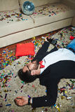 Wild New Year party. Middle-aged drunk man holding champagne bottle in hand while sleeping on floor covered with confetti after New Year party Stock Photo