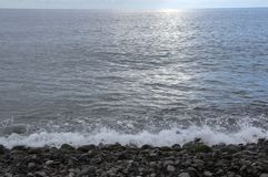 Pebbles beach with waves and sun reflection, blue sky, cloudy weather royalty free stock photos