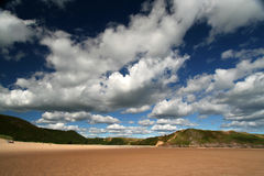 Wild open spaces. Wide angle shot of sandy beach with blue sky and white fluffy cumulus, shot with a polarizer royalty free stock photos