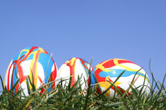 Wild painted Easter eggs. 3 Easter eggs in grass against  a bright blue sky Royalty Free Stock Photography
